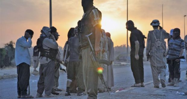 File photo of fighters of the Islamic State of Iraq and the Levant (ISIL) standing guard at a checkpoint in the northern Iraq city of Mosul