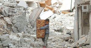 A boy carries belongings as he walks on rubble of damaged buildings in al-Kalaseh neighborhood of Aleppo