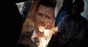 A member of the Free Syrian Army holds a burning portrait of embattled President Bashar al-Assad in Al-Qsair, 25kms southwest of the flashpoint city Homs, on January 25, 2012. Although heavily outnumbered and outgunned, the Free Syrian Army has increasingly launched bold attacks against regime forces and managed to seize control of some neighbourhoods of Homs. AFP PHOTO/ALESSIO ROMENZI (Photo credit should read Alessio Romenzi/AFP/Getty Images)