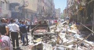 Syrians gather at the site of a double bombing attack on June 11, 2016 outside the Sayyida Zeinab shrine, which is revered by Shiites around the world, some ten kilometres south of the centre of Damascus, in the latest in repeated deadly strikes on the revered site. The official SANA news agency said a suicide bomber and a car bomb struck at the entrance to the shrine. / AFP PHOTO / STRINGER