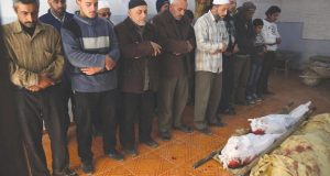 Syrians pray over the body of a woman and her two children, as regime aircraft pounded rebel-held areas near the Syrian capital, in rebel-held town of Jisreen, on the outskirts of the capital Damascus, on November 18, 2016. At least 11 people including four children were killed in air strikes on rebel-held areas near the Syrian capital, the Syrian Observatory for Human Rights said. / AFP PHOTO / AMER ALMOHIBANY
